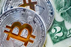 Symbolic bitcoin coins on a rare two dollar banknote. Exchange bitcoin for dollar. Close up shot stock images
