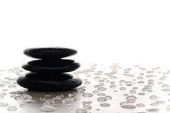 Symbolic Black Polished Stone Zen Meditation Cairn. Symbolic meditative Zen stone cairn for meditation and reflection over slab covered with water bubbles Stock Photos