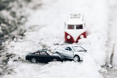 Symbolic car accident in winter on snow road staged with toy car. S Stock Photos
