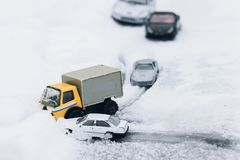 Symbolic car accident in winter on snow road staged with toy car. S Stock Images