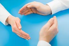 Symbolic circle. Human hands making symbolic circle on a blue background stock photos