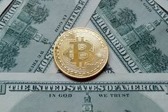 A symbolic coins of bitcoin on banknotes of one hundred dollars. Royalty Free Stock Photography