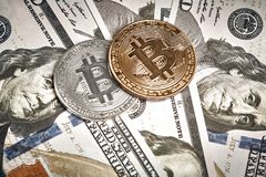 A symbolic coins of bitcoin on banknotes of one hundred dollars. Exchange bitcoin cash for a dollar. Flat lay. Top view. Still life stock photography
