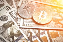 A symbolic coins of bitcoin on banknotes of one hundred dollars. Exchange bitcoin cash for a dollar. Sun flare. A symbolic coins of bitcoin on banknotes of one stock photo