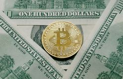 A symbolic coins of bitcoin on banknotes of one hundred dollars. Royalty Free Stock Photo