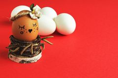 Self-centered light brown egg with satin flower in bed tones in nest of birch twigs and white eggs on bright red background. Minim stock photo