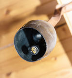 Symbolic cowbell hanging on the wooden beam Stock Photos
