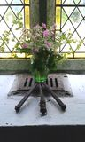 Symbolic display of wild flowers and crucifixion nails, in a church window, England stock images