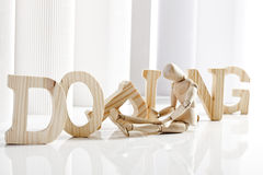Symbolic for doping, Wooden figurine sitting in front of wooden letters Royalty Free Stock Photography