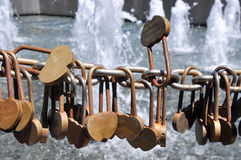 Symbolic Expression: Love Locks. Golden engraved love locks secured to chain link draped fence with a water fountain background outside the Bell Tower in Perth Royalty Free Stock Photography