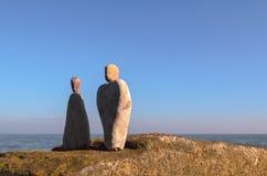 Symbolic figurines on seashore Royalty Free Stock Photos