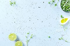 Symbolic food background with lime, pea sprouts, sea salt and frozen peas Stock Image