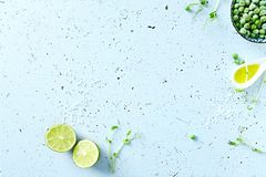 Symbolic food background with lime, pea sprouts, sea salt and frozen peas. Top view royalty free stock photo