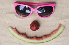 Symbolic happy summer face. Made out of fruit and sunglasses in the sand Royalty Free Stock Images