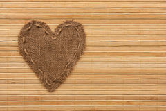 The symbolic heart of burlap lies on a bamboo mat. As a background Royalty Free Stock Photos