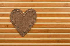 The symbolic heart of burlap lies on a bamboo mat. As a background Royalty Free Stock Images