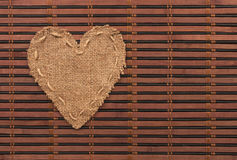 The symbolic heart of burlap lies on a bamboo mat. As a background Stock Image