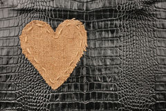The symbolic heart from burlap lies on a crocodile  leather Royalty Free Stock Photos