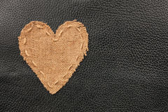 The symbolic heart from burlap lies on a natural leather Royalty Free Stock Images