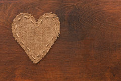 The symbolic heart of burlap lies on a wooden surface Royalty Free Stock Images