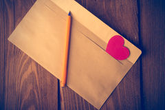Symbolic heart of cardboard inserted into the envelope. Royalty Free Stock Images