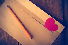 Symbolic heart of cardboard inserted into the envelope. Stock Photos
