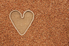 Symbolic heart made of rope lies on sackcloth and  buckwheat gra Royalty Free Stock Photography
