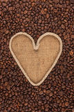 Symbolic heart made of rope lies on sackcloth and coffee beans. With space for your text Stock Images