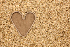 The symbolic heart made of rope lies on sackcloth and oats grain Royalty Free Stock Images
