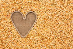 The symbolic heart made of rope lies on sackcloth and peas grain Royalty Free Stock Photography