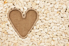 Symbolic heart made of rope lies on sackcloth and  pumpkin seeds Royalty Free Stock Photography