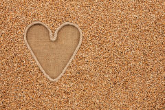 The symbolic heart made of rope lies on sackcloth and wheat grai Royalty Free Stock Image