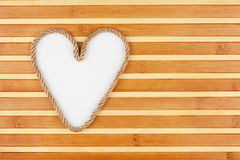 Symbolic heart made of rope lying on a bamboo mat Royalty Free Stock Image