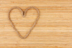 Symbolic heart made of rope lying on a bamboo mat. As background Stock Photography
