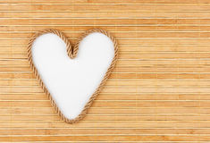 Symbolic heart made of rope lying on a bamboo mat. As background Royalty Free Stock Image