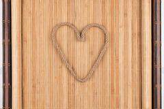 Symbolic heart made of rope lying on a furled bamboo mat. As background, conceptual image Royalty Free Stock Photos