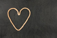 Symbolic heart made of rope lying on a natural leather Royalty Free Stock Photography