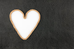 Symbolic heart made of rope lying on a natural leather Royalty Free Stock Photo