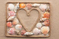 Symbolic heart made from rope and sea shells lying on the sand. As background stock photos
