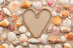 Symbolic heart made from rope and seashells lying on the sand. As background stock photography