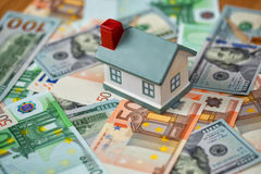 A symbolic house on the banknotes of Euro and Dollars Royalty Free Stock Photos