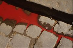 Symbolic image of revolution - blood in the gutters. Close view of blood flowing in the gutter of a war-torn town Stock Photos