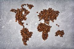 Symbolic image of world map made from roasted coffee beans. On gray concrete background stock image