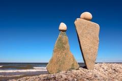 Symbolic man and woman. Symbolic figurines of man and woman at the seashore Royalty Free Stock Image