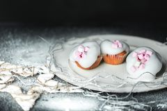Symbolic photo of sweet white, snowy Christmas. Sweet winter cupcakes with white, light sugar foam and pink marshmallows on the background of a Christmas royalty free stock photography