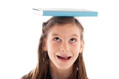 Symbolic picture: Girl holding a book on her head Stock Photos