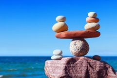 Concept of harmony and balance. Balance stones against the sea. Symbolic scales of stones against the background of the sea and blue sky. Concept of harmony and Royalty Free Stock Photos
