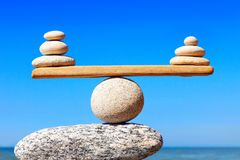 Concept of harmony and balance. Balance stones against the sea. Symbolic scales of stones on the background of the sea and blue sky. Concept of harmony and Stock Image