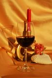 Symbolic wish for love. Red wine, candle, rose and white heart shaped object on an elegant golden background, symbolic love image Royalty Free Stock Photo