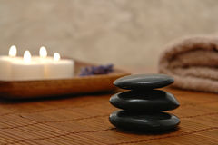 Symbolic Zen Inspired Stone Cairn in a Spa. Symbolic meditative Zen inspired black polished stone cairn with soft glowing flame burning candles and towel for a Royalty Free Stock Photography